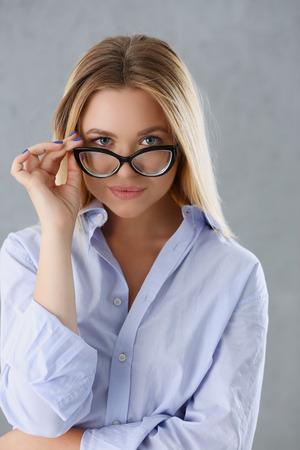 Portret van een sexy vrouw in een man shirt dragen van een bril op een grijze achtergrond kijkt naar de camera en glimlachend kijken advies geven wil bezwaren worden niet geaccepteerd