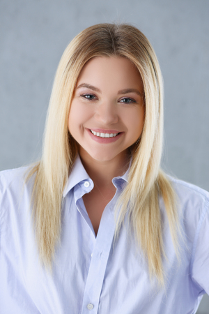 Portrait of a sexy woman in a mans shirt wearing on a gray background looks at the camera and smiling look advice to give wants objections are not accepted Stock Photo