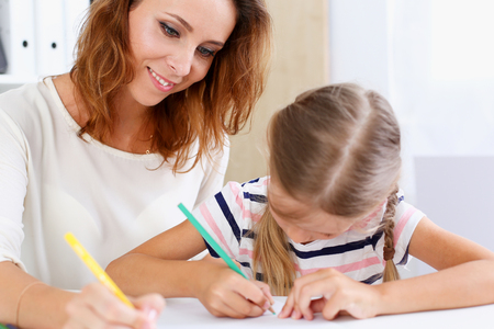 sitter: Blond little girl hold in arm pencil drawing something together with mom. Beautiful female young artist, minor baby-sitter, art joy, juvenile development, parent lifestyle, youth, painter concept