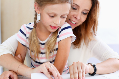 Blond smiling little girl make paper plane together with mom. Beautiful female young dreamer, minor baby-sitter, DIY aircraft, juvenile development, parent lifestyle, youth, adventure concept Standard-Bild