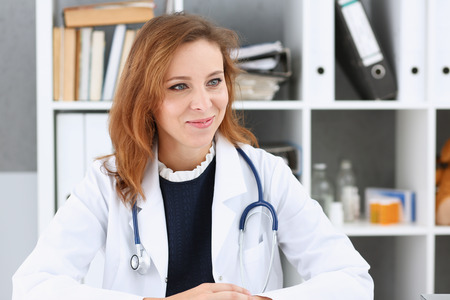 Beautiful smiling female doctor sit at workplace. Physical and disease prevention, patient aid, exam visit, 911, ward round, prescribe remedy, healthy lifestyle, consultant profession concept
