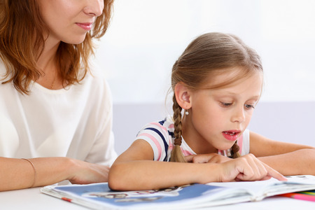Blond little reading together with mom. Beautiful female young reader, minor baby-sitter, fairy tale joy, story, juvenile development, parent lifestyle, youth concept