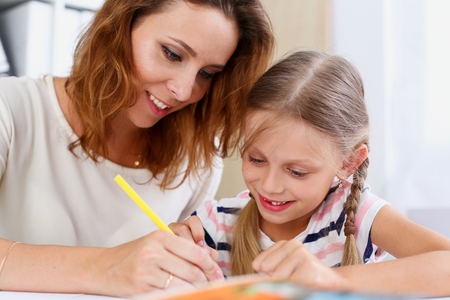 Blond smiling little girl hold in arm pencil drawing something together with mom. Beautiful female young artist, minor baby-sitter, art joy, juvenile development, parent lifestyle, youth, painter