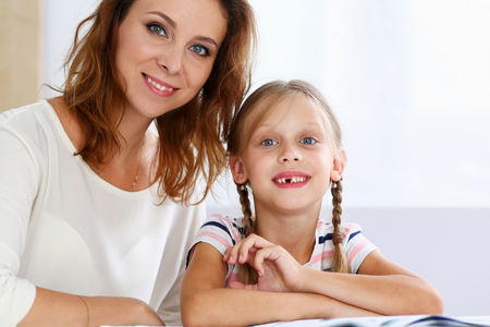 Blond smiling little reading together with mom. Beautiful female young reader, minor baby-sitter, fairy tale joy, story, juvenile development, parent lifestyle, youth concept