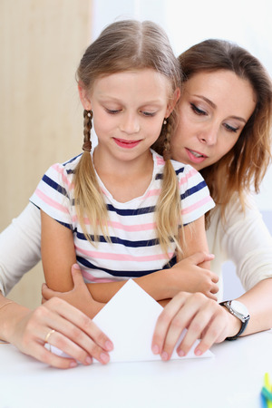 sitter: Blond smiling little girl make paper plane together with mom. Beautiful female young dreamer, minor baby-sitter, DIY aircraft, juvenile development, parent lifestyle, youth, adventure concept Stock Photo
