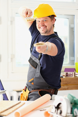 Arm of smiling worker hold brush portrait. Manual job workplace, DIY inspiration, improvement, fix shop, yellow helmet, hard hat, joinery startup idea, industrial education, profession career concept