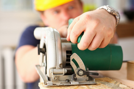 Arms of worker using electric saw closeup. Manual job workplace, DIY inspiration, improvement, fix shop, yellow helmet, hard hat, joinery startup idea, industrial education, profession career concept
