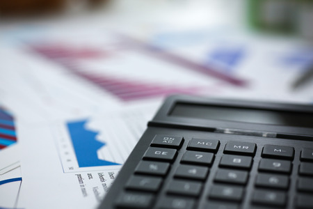 Black calculator and financial statistics on infographics at office table closeup. Internal Revenue Service inspector sum check, irs investigation, earnings, savings, loan and credit concept