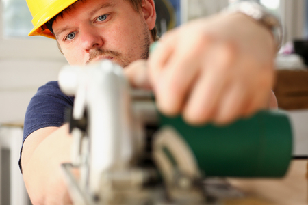 Worker using electric saw portrait. Manual job workplace, DIY inspiration, improvement, fix shop, yellow helmet, hard hat, joinery startup idea, industrial education, profession career concept