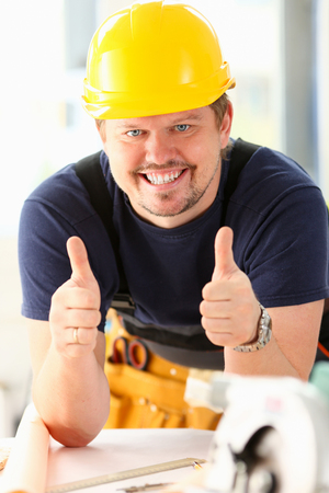 Smiling worker in yellow helmet show confirm sign with thumb up at arm portrait. Manual job, DIY inspiration, joinery startup idea, fix shop, hard hat, industrial education, profession career concept