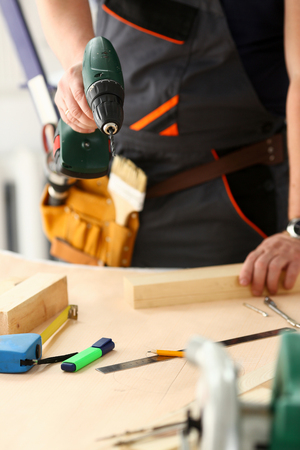 Arms of worker using electric drill closeup. Manual job, DIY inspiration, improvement job, fix shop, yellow helmet, joinery startup idea, industrial education, profession career concept