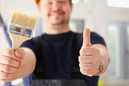 Arms of worker hold paint brush and show confirm sign with thumb up closeup. Manual job, DIY inspiration, joinery startup idea, fix shop, hard hat, industrial education, profession career concept