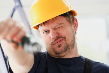 Worker using electric drill portrait. Manual job, DIY inspiration, improvement, fix shop, yellow helmet, joinery startup idea, industrial education, profession career concept