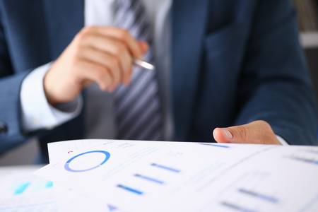 Male hands hold documents with financial statistics at office workspace closeup. White collar check money papers, stock exchange market, internal Revenue Service inspector, earning list concept
