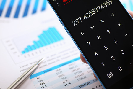 Smartphone calculator and financial statistics ondisplay tablet at office table closeup. Internal Revenue Service inspector sum check, irs investigation, earnings, savings, loan and credit concept Stock Photo