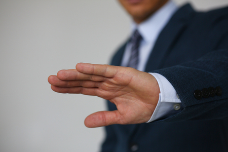 Gesture male hand rejection says no male businessman in a suit on a gray background I will not categorically claim