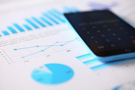 Calculatrice de Smartphone et statistiques financières ondisplay tablette au bureau table closeup. Inspecteur de revenu de l'Internal Revenue Service, IRs enquête, gains, épargne, concept de prêt et de crédit