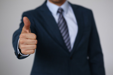 Male hand showing OK or confirm sign with thumb up during conference closeup. High level and quality product, serious offer, mediation solution, happy client, creative adviser participation concept Archivio Fotografico