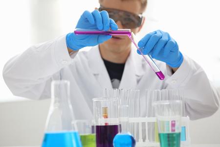 Un químico masculino sostiene un tubo de vidrio de prueba en su mano, desborda una solución líquida de permanganato de potasio conduce una reacción de análisis que toma varias versiones de reactivos utilizando la fabricación de productos químicos