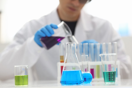 Ein männlicher Chemiker hält ein Reagenzglas aus Glas in der Hand. Eine flüssige Lösung von Kaliumpermanganat führt eine Analysereaktion durch, bei der verschiedene Versionen von Reagenzien mittels chemischer Herstellung verwendet werden Standard-Bild