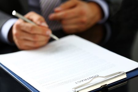 Male arm in suit and tie fill form clipped to pad with silver pen closeup. Sign gesture, read pact, sale agent, bank job, make note, loan credit mortgage investment, finance chief, legal law concept