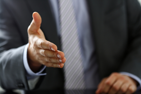 Man in suit and tie give hand as hello in office closeup. Friend welcome, mediation offer, positive introduction, thanks gesture, summit participate approval, motivation, male arm, strike bargain 免版税图像