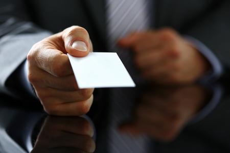 De mannelijke wapen in kostuum geeft leeg visitekaartje aan bezoekerclose-up. Witte kraag collega's bedrijfsnaam uitwisseling, sollicitatiegesprek, verkoopmedewerker id, uitvoerend of ceo, financiële ondersteuning, formeel identiteitsconcept