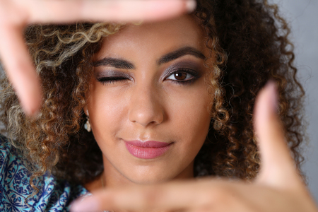 picture framing: Beautiful black woman portrait. She put her hand around the frame as if she were photographing a beauty fashion style mulatto curly hair with white locks eyes look into the camera