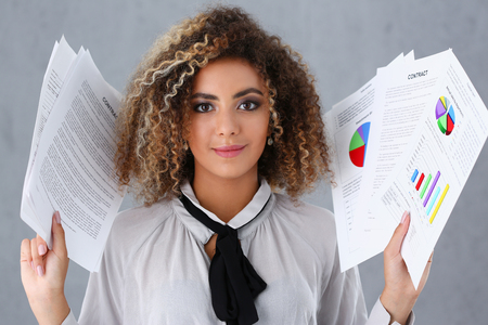 Beautiful black woman portrait. Holds paper documents with financial statistics fashion style mulatto curly hair with white locks eye view of the camera lot of work