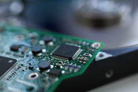 Electronic board with microchips on a hard drive background in a repair workshop background