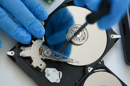 hard disk: Male repairman wearing blue gloves dismantles specialized professional screwdriver  hard drive. Performs fault diagnostics and performs urgent repairs recovery of lost data during deletion HDD closeup Stock Photo