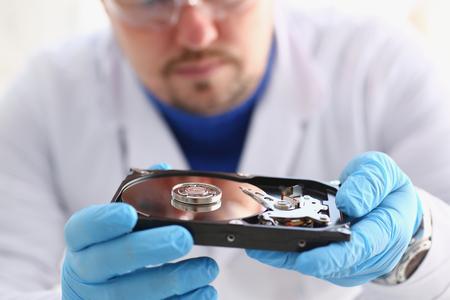 Ein männlicher Schlosser, der blaue Handschuhe trägt, hält eine Festplatte vom Computer oder vom Laptop in den Händen. Führt Fehlerdiagnose durch und führt dringende Reparaturen durch Wiederherstellung von verlorenen Daten während des Löschens