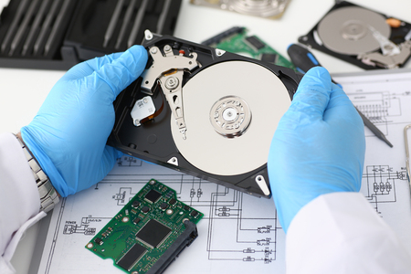 A male repairman wearing blue gloves is holding a hard drive from computer or laptop in hands. Performs fault diagnostics and performs urgent repairs recovery of lost data during deletion HDD closeup Stok Fotoğraf