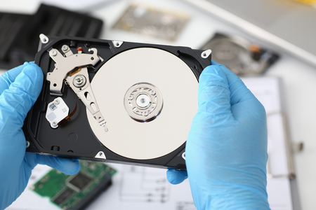 A male repairman wearing blue gloves is holding a hard drive from computer or laptop in hands. Performs fault diagnostics and performs urgent repairs recovery of lost data during deletion HDD closeup Stock Photo