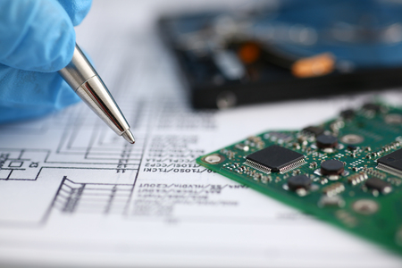 processors: The male hand of the repairman holds a pen, compares the electronic schematic with the details of the printed circuit board