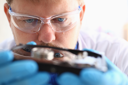 hard disk: A male repairman wearing blue gloves is holding a hard drive from computer or laptop in hands. Performs fault diagnostics and performs urgent repairs recovery of lost data during deletion HDD closeup Stock Photo