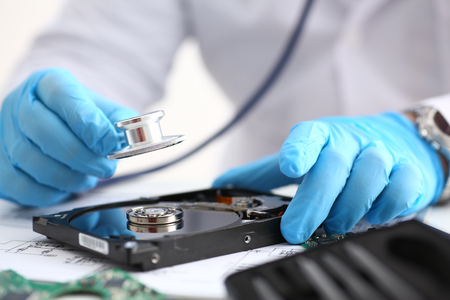 A male repairman wearing blue gloves holding stethoscope on hard drive from computer laptop in hands. Performs fault diagnostics and performs urgent repairs recovery lost data during deletion closeup
