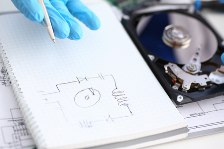 A male repairman in blue protective gloves examines an electrical printers schematic of the hard disk unit that performs its diagnostics and repair Stock Photo