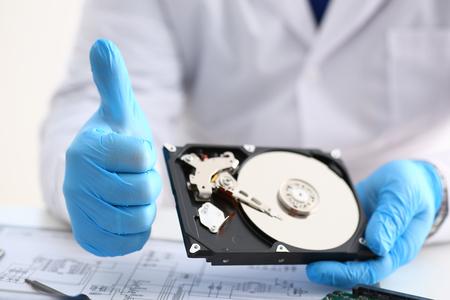 Hombre reparador con guantes azules sostiene el disco duro de la computadora portátil en las manos muestran los pulgares OK. Realiza diagnósticos, realiza reparaciones urgentes, recupera datos perdidos durante la eliminación de HDD closeup