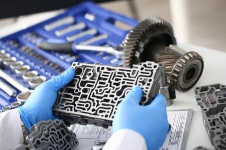 Der Autoreparaturdienst-Schlosser in den automatischen Getrieben hält in seiner Hand in den blauen Schutzhandschuhen das hydroblock Detail dehydrates die Diagnosen und schätzt die Detailtestübertragungnahaufnahme Standard-Bild - 87836299