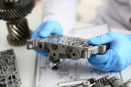 The auto repair service repairman in automatic gearboxes holds in his hand in blue protective gloves the hydroblock detail dehydrates the diagnostics and estimates the detail test transmission closeup Stock Photo