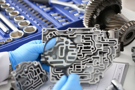 Auto service repairman for automatic gearboxes keeps in hand in blue protective gloves examines through the lens the detail of the hydraulic unit performs diagnostics and estimates the detail closeup Stock Photo