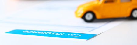 Insurance form lying on table with unrecognizable yellow toy car closeup. Driver money loss prevention, secure road trip, harmless drive idea, owner protective offer concept