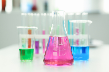 Chemical industry bulb with blue magenta pink liquid lab tubes stand on the table in the laboratory of liquid testing test development substances poisons additives stabilizers flavors house cleaning Stock Photo