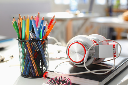 electronic book: Headphones diary and pencil lie on the desk of the concept of remote distance education listen to music compose tunes for sale school sound training instruments thematic studing sound recording studio Stock Photo