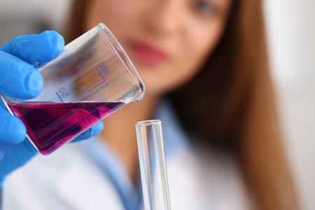 Female chemist holds test tube of glass in his hand overflows a liquid solution of potassium permanganate conducts an analysis reaction takes various versions of reagents using chemical manufacturing