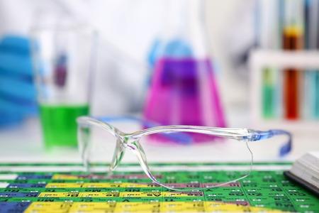 Beschermende chirurgische of laboratoriumbril liggend op het periodiek systeem