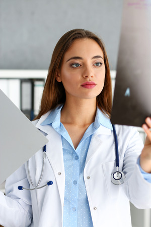 Beautiful female doctor hold in arm xray picture