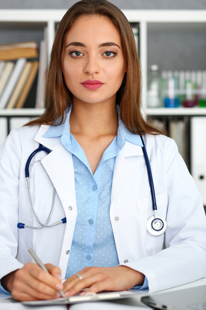 Female doctor hold hold in arm silver pen and pad Stock Photo