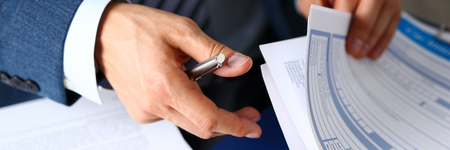Male arm in suit offer insurance form clipped to pad